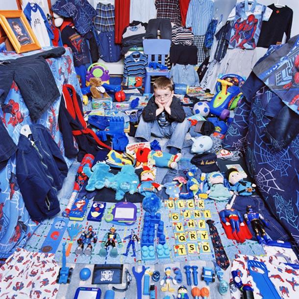 Petite garçon entourée de jouets et d'habits bleus