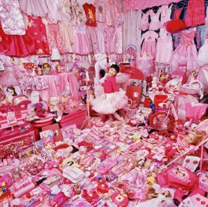 Petite fille entourée de jouets et d'habits roses